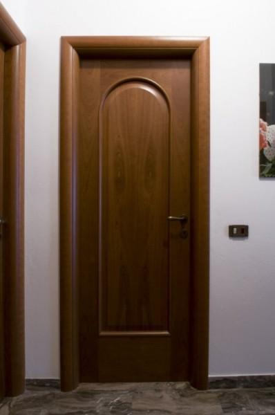 Porta in ciliegio con specchiatura ad arco cieca verniciata tinta noce