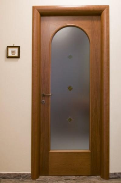 Porta in ciliegio con specchiatura ad arco a vetro verniciata tinta noce con telaietto fermavetro tondo