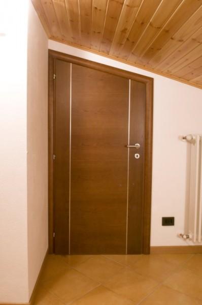 Porta in ciliegio cieca verniciata in tinta noce con impiallaciatura orizzontale e due inserti verticali in alluminio satinato